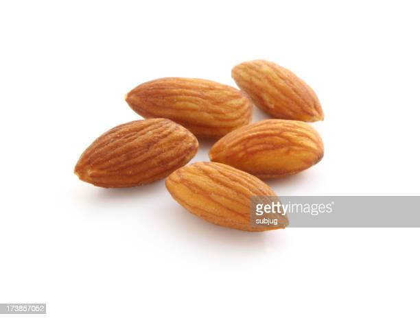 Picture of five almonds laid out in a white background