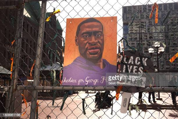 Picture of George Floyd hangs on a fence barrier that surrounds the Hennepin County Government Center as the trial of former Minneapolis police...