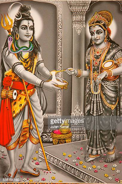 picture of hindu god shiva with annapurna (parvati giving food) - shiva stock photos and pictures