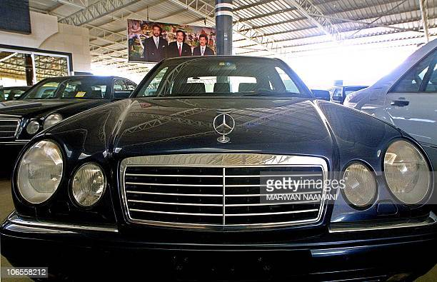 A picture of Iraqi President Saddam Hussein his sons Uday and Qusay hangs in the background as Mercedes cars are displayed at the Sardar dealership...