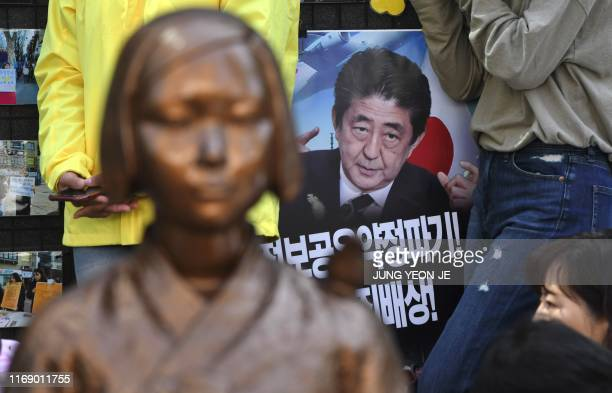 """Picture of Japanese Prime Minister Shinzo Abe is seen behind a statue of a teenage girl symbolising former """"comfort women"""", who served as sex slaves..."""