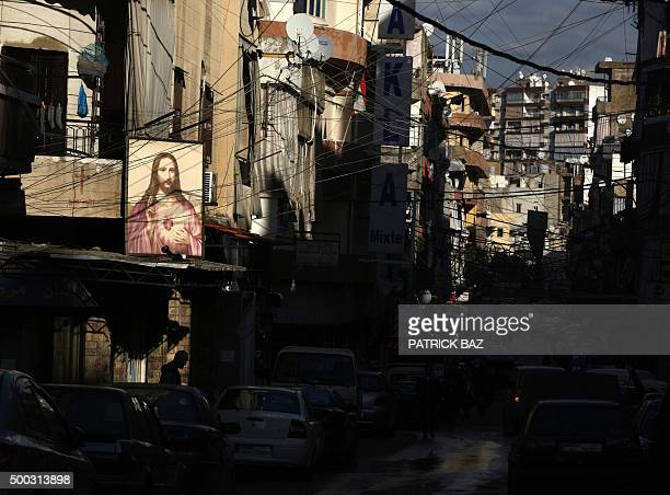 TOPSHOT A picture of Jesus Christ hangs on a wall of a building in a mixed Christian and Shiite Muslim neighborhood in an eastern suburb of the...