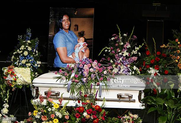 A picture of Joanie Harper and her infant son Marshall James is displayed over her casket at the funeral for her four family members who were found...