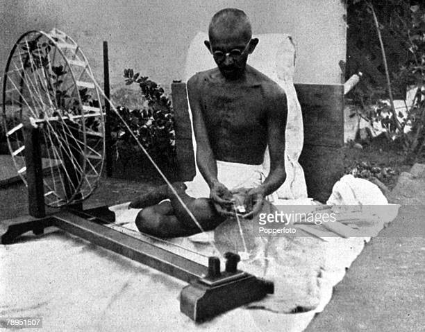 A picture of Mahatma Gandhi the Indian political and spiritual leader guru and social reformer at his spinning wheel
