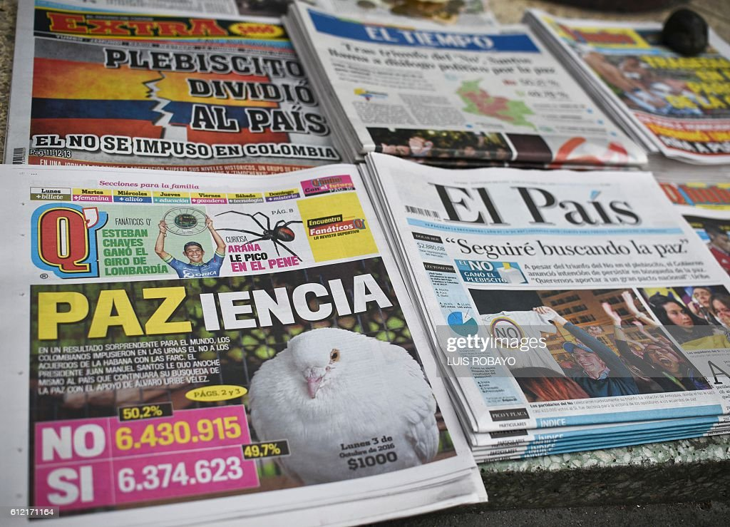 Picture of newspapers announcing the results of the referendum that surprisingly said 'No' to the peace agreement between the Colombian government and the FARC guerrillas in Cali, Colombia, taken on October 3, 2016. The peace accord was supposed to end the last major armed conflict in the Western hemisphere. / AFP / LUIS