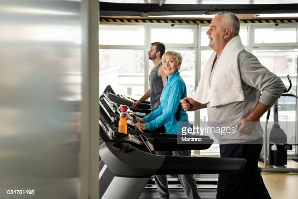 picture of people running on treadmill in gym - cardiovascular exercise stock pictures, royalty-free photos & images