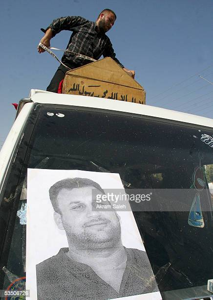 A picture of Reuters TV soundman Waleed Khaled is seen as his casket is loaded on a bus for burial on August 29 2005 in Baghdad Iraq A Reuters...