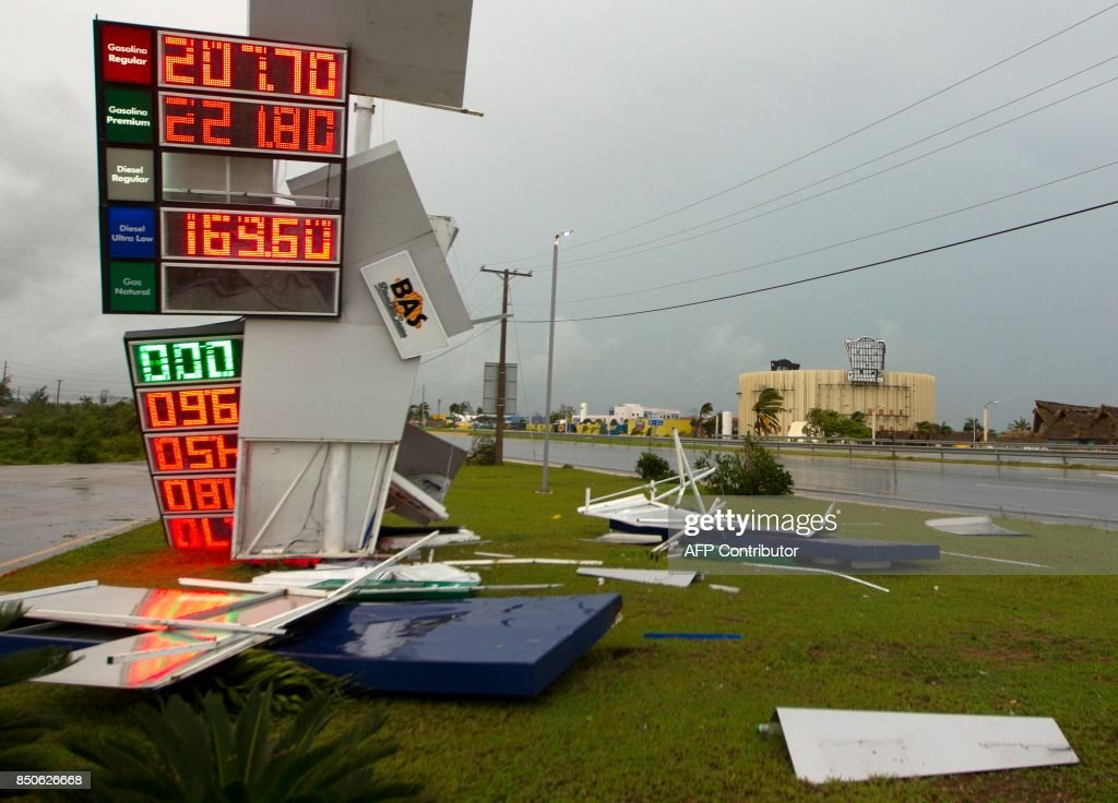 Picture of signs of a station knocked down by strongs winds of Hurricane Maria in Punta Cana, in the eastermost tip of the Dominican Republic as the hurricane passes just north of the La Espanola island the country shares with Haiti, on September 21, 2017. After cutting a devastating path across Puerto Rico, the now Category Three storm, packing 115 mile (185 kilometre) per hour winds, is passing north of the Dominican Republic as it moves toward the Turks and Caicos Islands, according to the US National Hurricane Centre. / AFP PHOTO / Erika SANTELICES