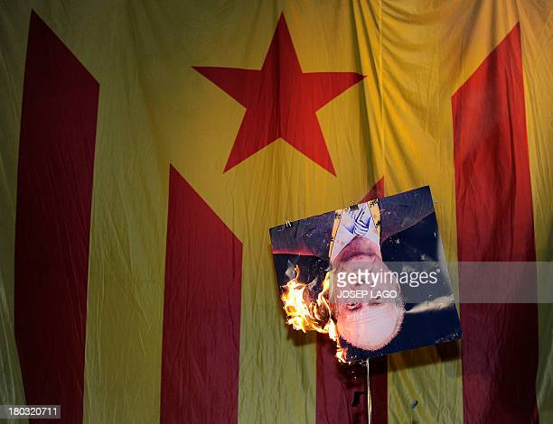 A picture of Spain's King Juan Carlos burns after a member of radical leftwing Catalan independentist political party CUP sets its fire in front of...