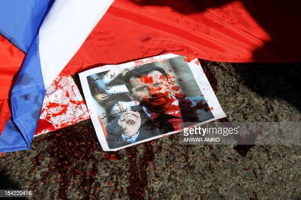A picture of Syria's embattled President Bashar alAssad sprayed with red paint lies on the ground next to a Russian flag about to be set on fire by...