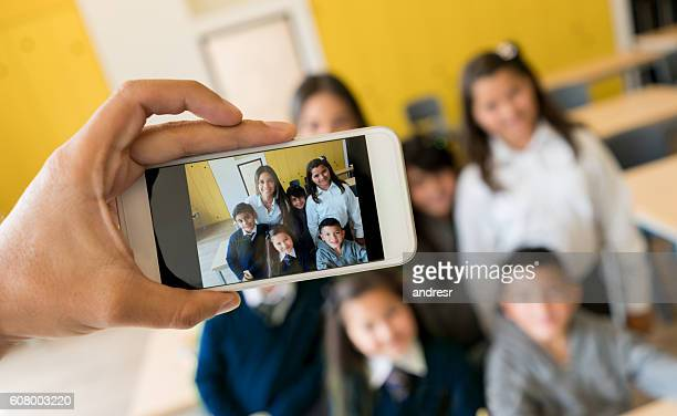 Picture of teacher and students with a cell phone