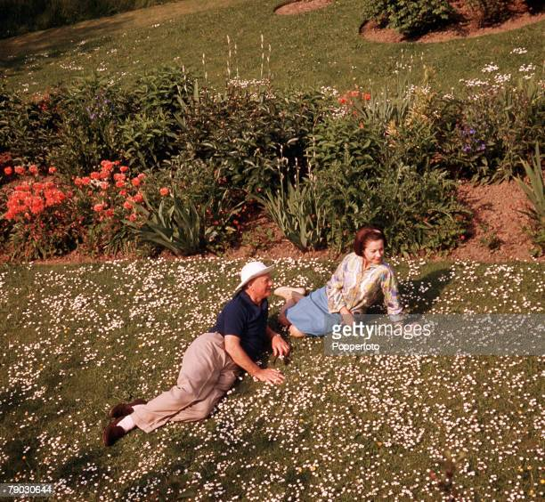 A picture of the American actress Vivien Leigh relaxing with another man outside lying on a lawn full of daisies