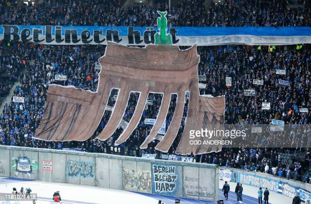 Picture of the Brandenburg Gate is spread out over the suporters' tribunes and a mock-up of the former Berlin Wall during a ceremony before the start...