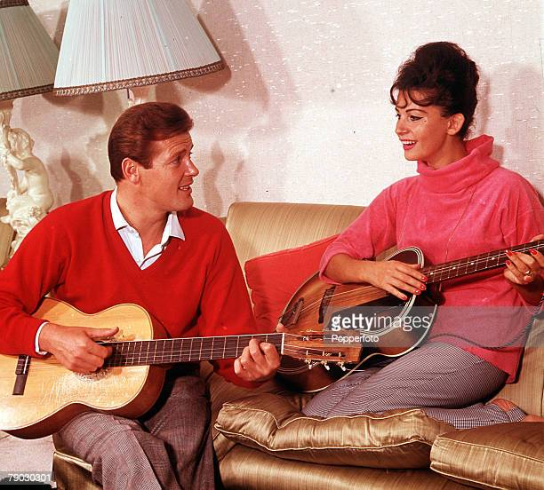 1964 A picture of the British actor Roger Moore with the actress Luisa Mattioli whilst they are both playing the guitar