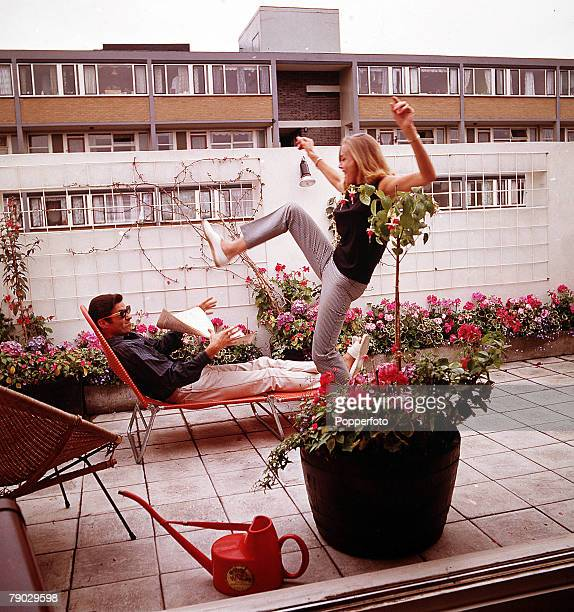 A picture of the British actress Honor Blackman in an urban outside patio area whilst doing a kick with her leg held high