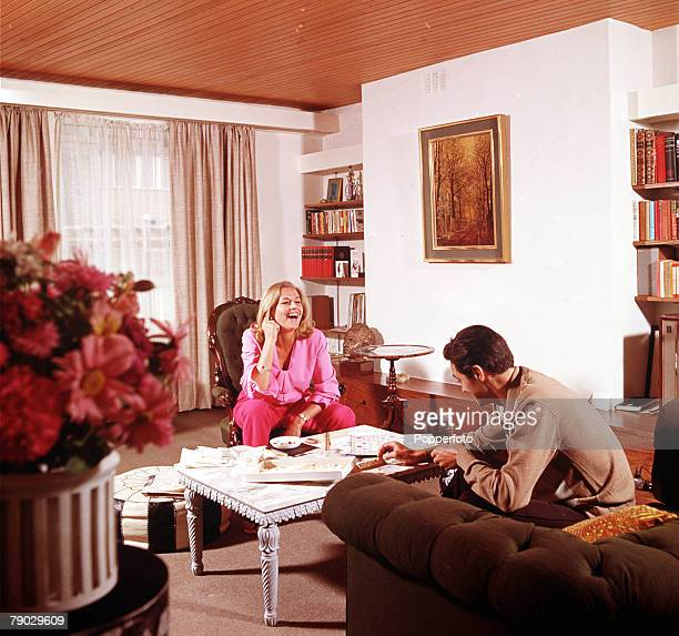 A picture of the British actress Honor Blackman sitting whilst relaxing and laughing in a living room