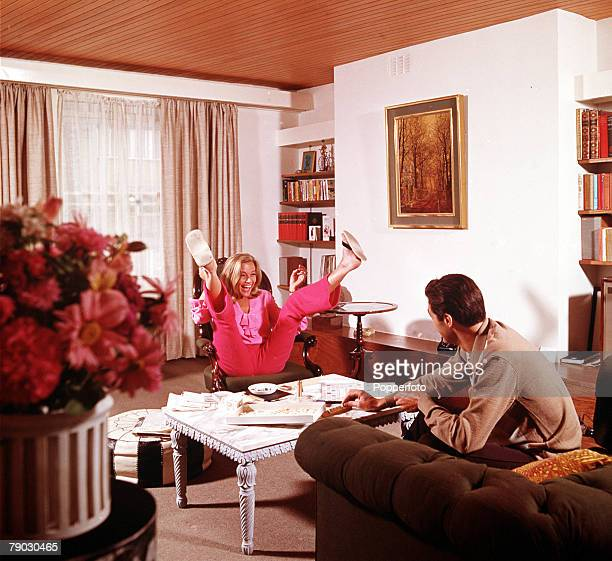 A picture of the British actress Honor Blackman sitting with her legs akimbo in the air whilst relaxing in a living room
