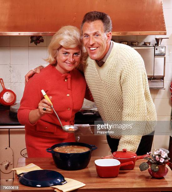 A picture of the British television presenter Bruce Forsyth smiling at the camera at home with his arm around his wife who is displaying one of three...