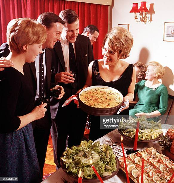 A picture of the British television presenter Judith Chalmers at a buffet party with another British television presenter Michael Aspel and his wife...