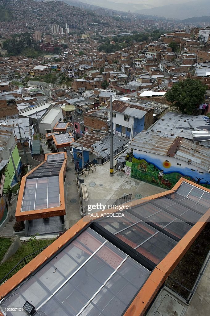 """Picture of the covered escalators at Comuna 13 neighbourhood, one of the poorest and most violent areas of the northeastern Colombian city of Medellin, Antioquia department, Colombia on March 1, 2013. Medellin, which competed with New York and Tel Aviv, was chosen by popular vote through the internet, as the """"Innovative City of the Year"""" during the City of the Year contest, organized by The Wall Street Journal and Citigroup. The distinction was basically made for its modern transportation system, its public library, escalators built in a shantytown and schools that have allowed the integration of society. AFP PHOTO/Raul ARBOLEDA"""