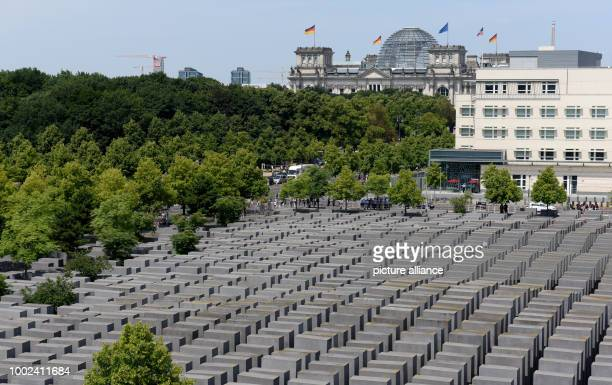 Picture of the Holocaust Memorial with the Reichstag in the background taken in Berlin Germany 19 July 2017 The AmericanEmbassy can be seen on the...