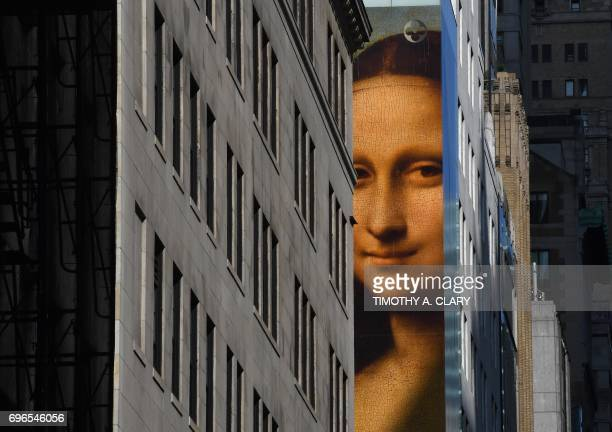 A picture of the Mona Lisa painting hangs on the side of the Louis Vuitton Store on 5th Avenue in New York on June 15 2017 to promote the Women's Da...