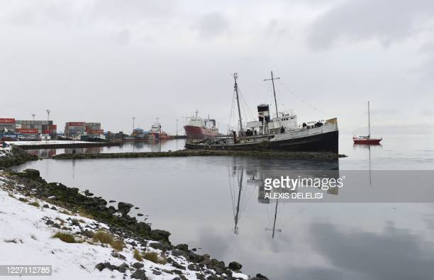 Picture of the Saint Christopher tugboat seen near the Echizen Maru fishing trawler which remains docked in the Ushuaia harbour in Tierra del Fuego...