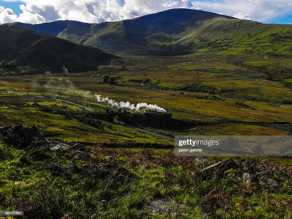 CONTENT] A picture of the Snowdon mountain railway steam train in Wales on its return trip over a small bridge