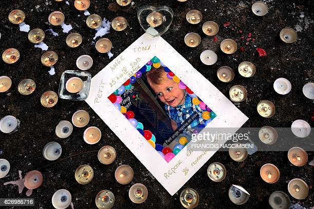 Picture of Tony, a child who died on November 26, 2016 at the age of 3 after being hit several times by his father-in-law, is surrounded by candles...