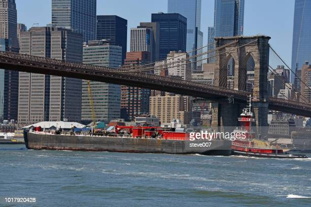 picture of tugboat and barge going southbound on the east river just before passing the brooklyn bridge. photo taken sunday july 8, 2018. - tugboat stock photos and pictures