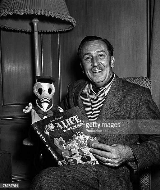 1951 A picture of US film producer and cartoonist Walt Disney at Dorchester reading a book with a model toy of Donald Duck