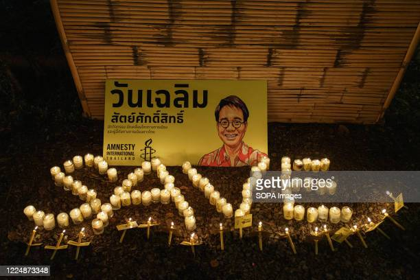 """Picture of Wanchalearm Satsaksit is seen with candles lit forming the word """"SAVE"""" during the one month abduction anniversary of the Thai critic...."""