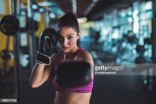 picture of woman doing a punch move at the gym - fighting stance stock pictures, royalty-free photos & images