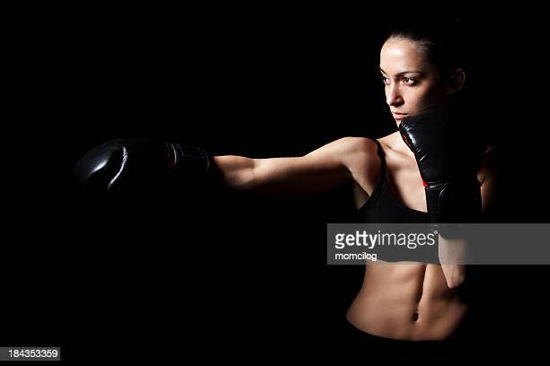 Picture of woman doing a punch move on black background