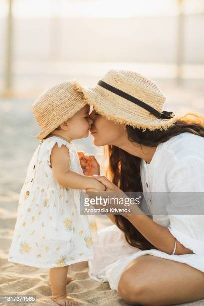 picture perfect mother daughter moment on the beach, gently touching and holding hands - peettante stockfoto's en -beelden