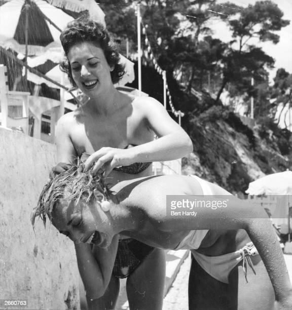 Picture Post model Jackie washes her friend's hair under a beach shower at Cap Ferrat Original Publication Picture Post 7850 The Secret Of Five Girls...
