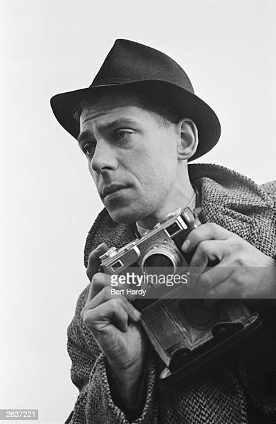 Picture Post photographer Bert Hardy on an assignment, February 1941. He is using a Contax II 35 mm rangefinder camera. Original Publication: Picture...