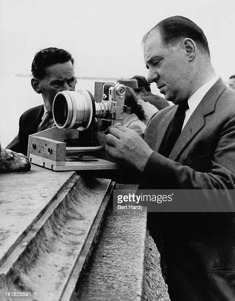 Picture Post photographer Bert Hardy with a Cinemascope anamorphic lens mounted on his Contax camera, Southend, Essex, August 1954. Original...