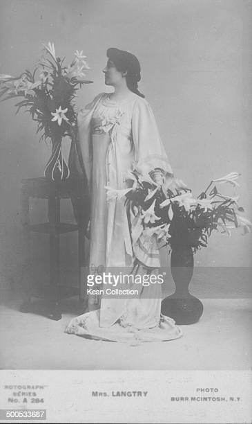 Picture postcard portrait of actress Lillie Langtry posing with two vases of lilies circa 18801900