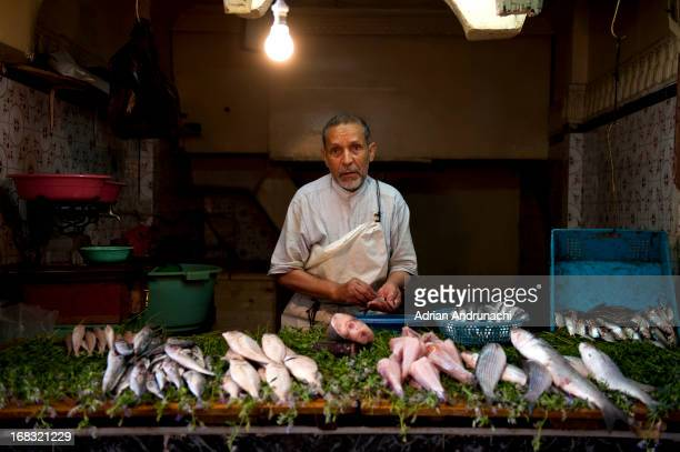Picture refers to a Moroccan fisherman who sales his merchandise in a small shop on one of the crowded street of Marrakesh's Medina.