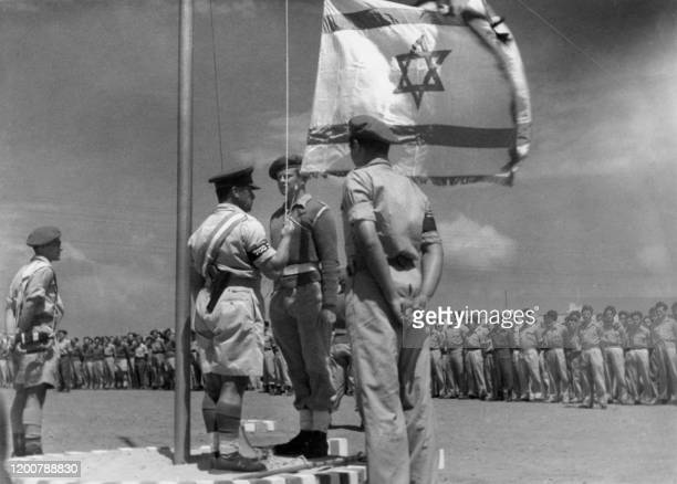 Picture released 08 June 1948 shows an Israeli officer raising the National Flag for the first time during the celebration of the birth of the...