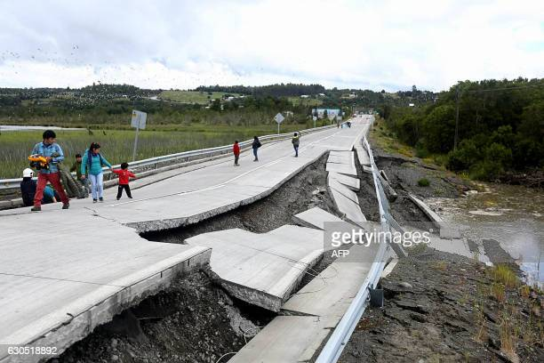People inspect damage caused on highway 5 south on Chiloe Island off the Pacific coast of southern Chile by a 77magnitude earthquake on December 25...