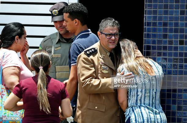 TOPSHOT Picture released by Brazilian newspaper O Popular showing a Military Police officer comforting a woman at the scene of a shooting at the...