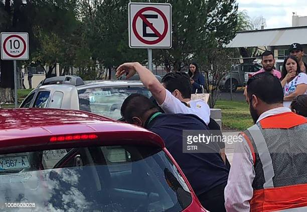 Picture released by Contacto Hoy showing a man being rushed into a vehicle at the airport of Durango in northern Mexico after a plane carrying 97...
