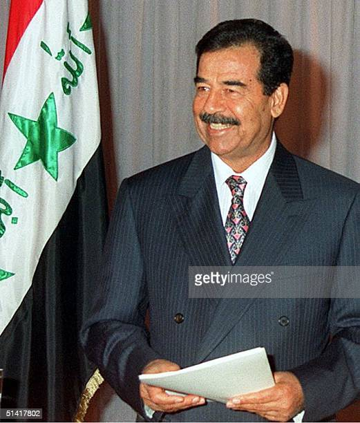 Picture released by INA showing Iraqi President Saddam Hussein smiling before addressing Iraqis via television 08 August on the 10th anniversary of...