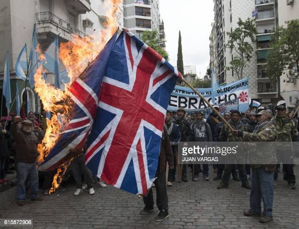 Picture released by Noticias Argentinas showing members of the Quebracho Patriotic Revolutionary Movement burning Union flags in front of the British...