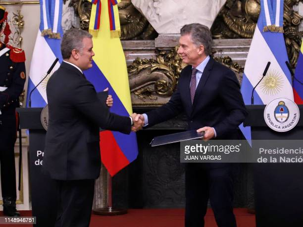 Picture released by Noticias showing Argentine President Mauricio Macri and his Colombian counterpart Ivan Duque exchange documents after signing...