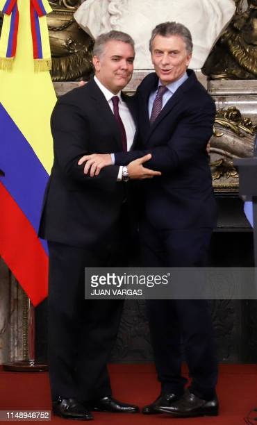 Picture released by Noticias showing Argentine President Mauricio Macri and his Colombian counterpart Ivan Duque embrace during a meeting at Casa...