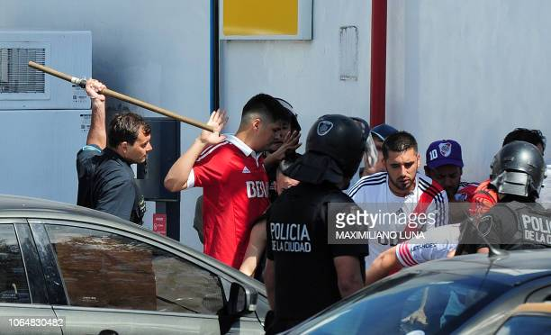 Picture released by Telam showing police officers and fans of River Plate at a gate of the the Monumental stadium in Buenos Aires, on November 24,...