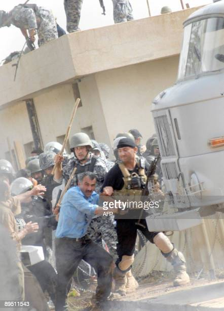 A picture released by the People's Mujahedeen late on July 29 shows Iraqi security forces clashing with a member of the Iranian oppositioninexile at...